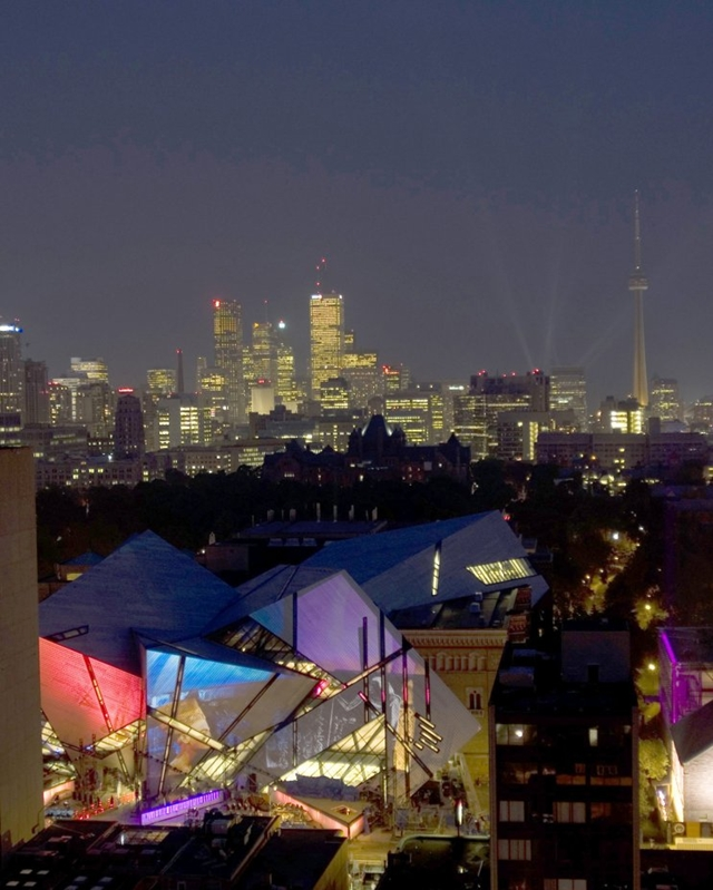 Royal Ontario Museum by Studio Daniel Libeskind at night with colorful lights and toronto skyline in the background