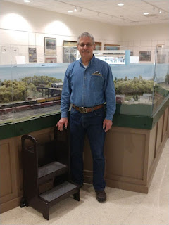 Man wearing jeans and long-sleeved denim shirt with Railroad Museum logo. He is standing in front of a large model railroad layout.