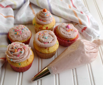 cupcakes with a variety of frosting decoration styles and piping bag