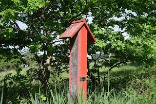 Ein rotes Insektenhotel steht auf einer Wiese am Wegesrand