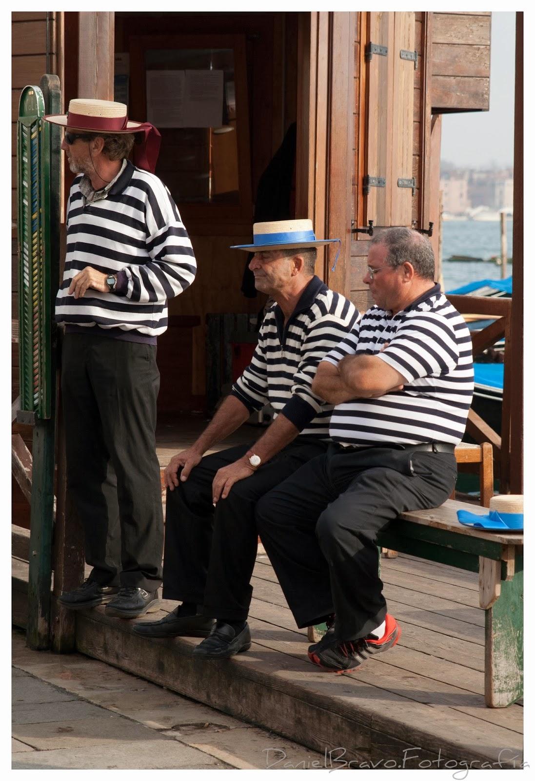 Tres gondoleros vestidos con traje típico reunidos y sentados fumando