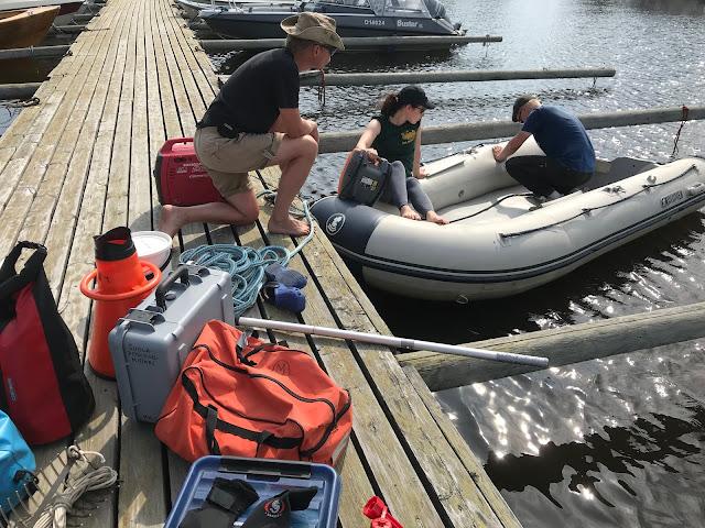 Kolme ihmistä lastaa tarvikkeet takaisin kumiveneeseen laiturilta.