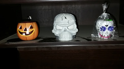 A tin vintage Jack-o-lantern, a skull lantern and a Day of the Dead candy skull cup.