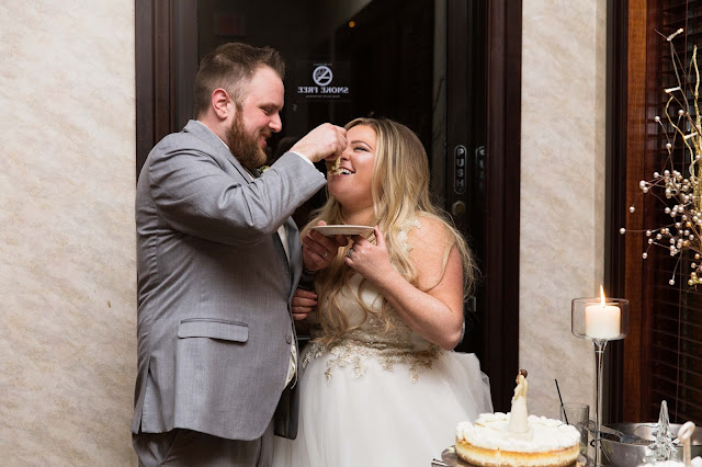 bride and groom feeding cake at italian american cultural center in Clinton Township