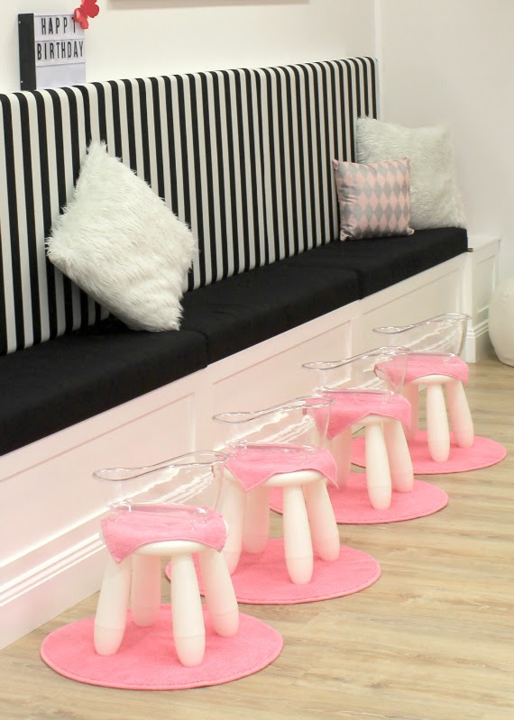 Image of pamper spa area for birthday parties with pink foot spas and striped lounge suite