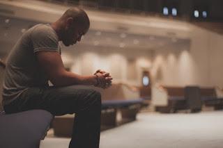 un individ care stă liniștit într-o sală de biserică - imagine preluată de pe churchleaders.com