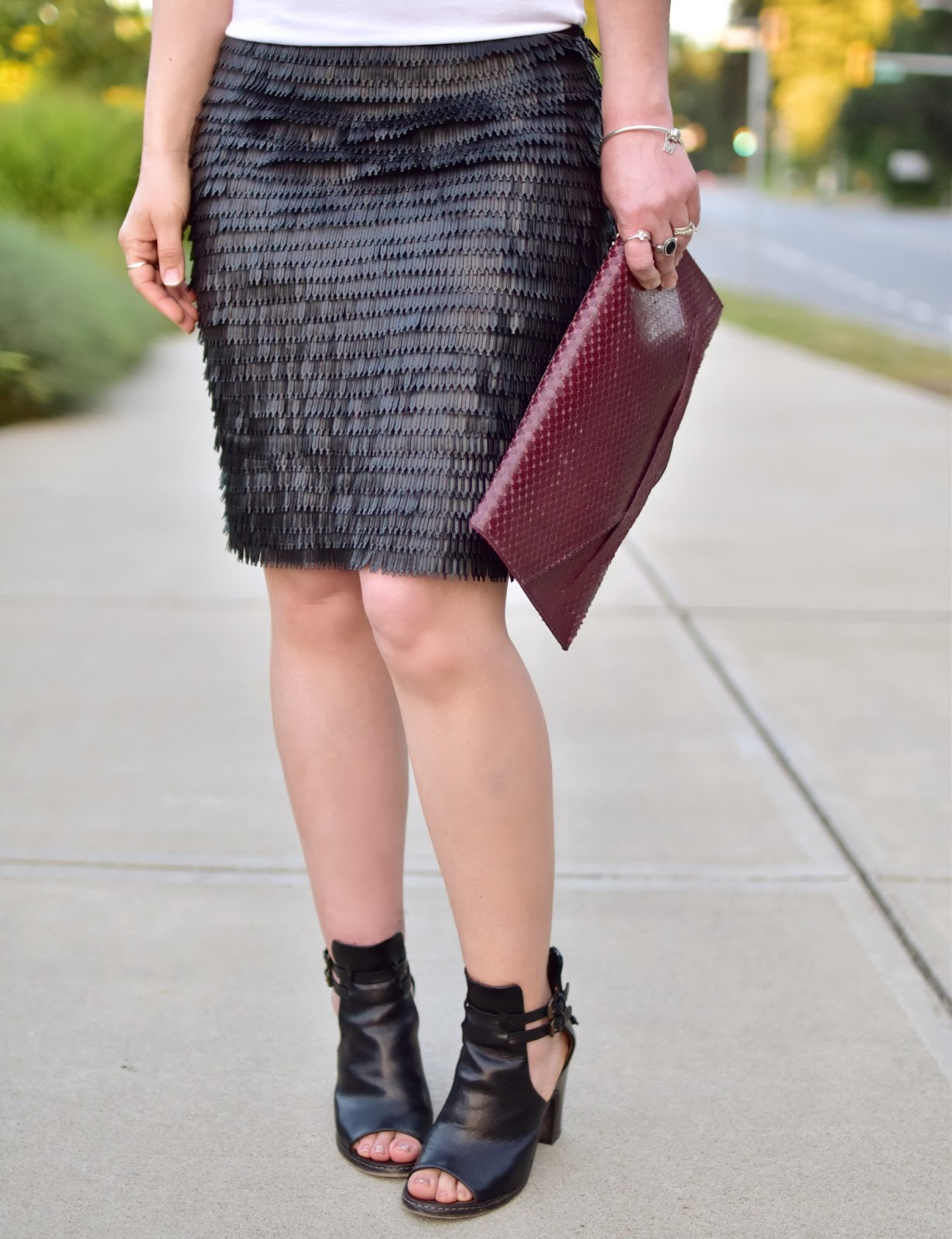 fish-scale-textured pleather skirt, cut-out booties, and faux-snake clutch
