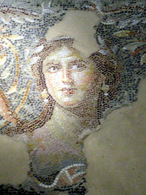 Roman mosaic portrait depicting a captivating woman adorned with earrings and a laurel garland, Triclium of the Roman Villa, Sepphoris, Galilee, Israel.
