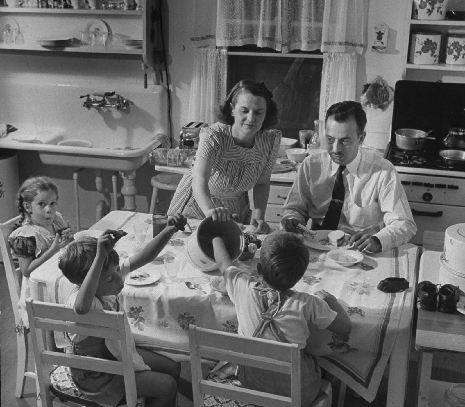 Jane serving lunch to her husband Gilbert, who has come home from the office a few minutes away, and her ever-present kids.