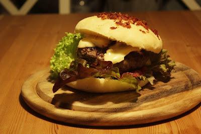 Rindfleischburger auf dreierlei Salat mit Rosmarin-Mayonnaise, mit Pflaumen-Zwiebel-Chutney und würzigem Camembert im Baconbrötchen.