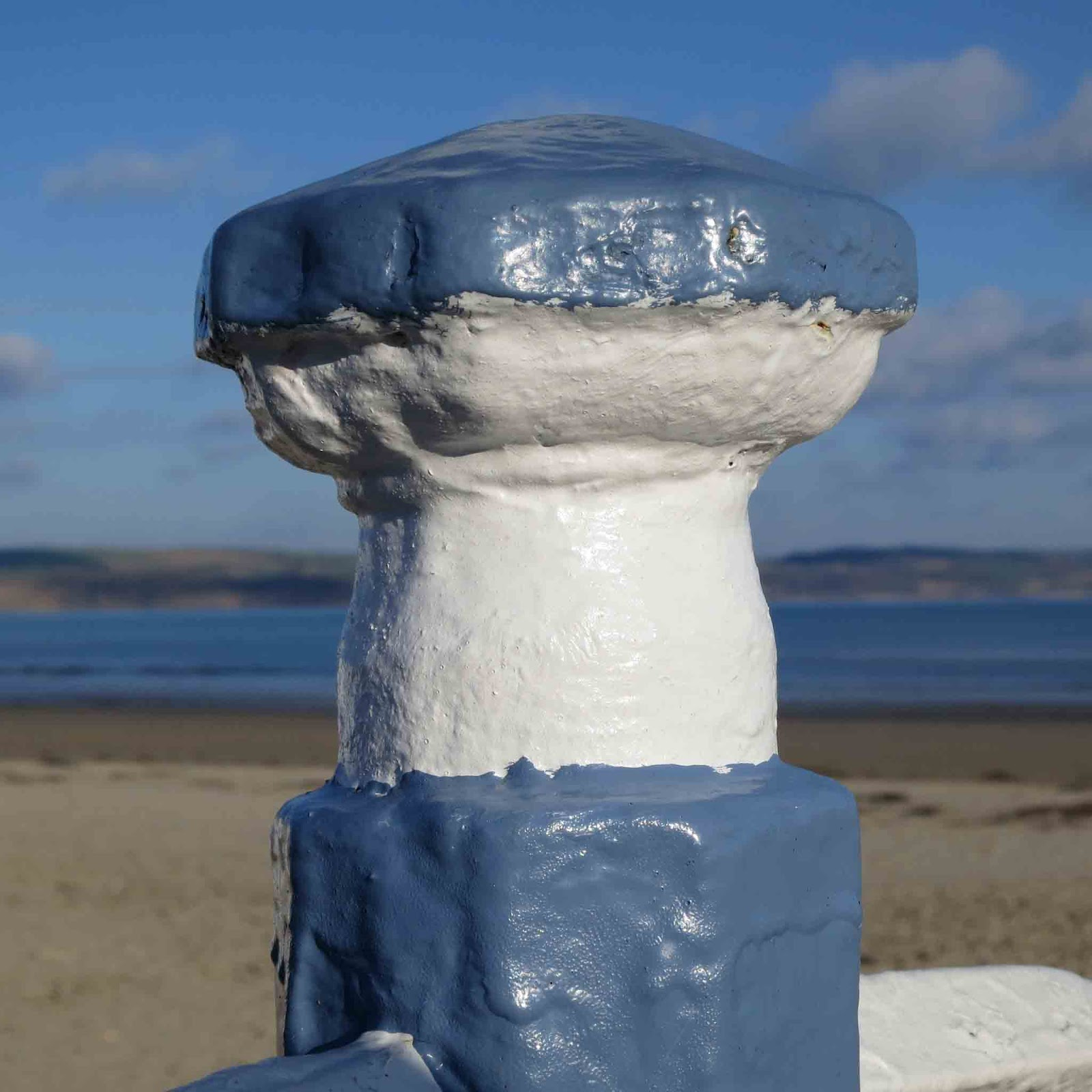 Blue and white post on handrail leading down to an English beach.