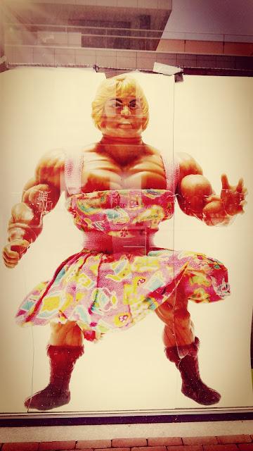 Poster van gespierde man met roze gebloemde jurk aan.