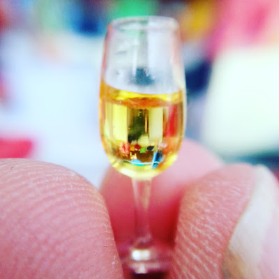 Macro photograph of a one-twelfth scale glass of wine held by several fingers.
