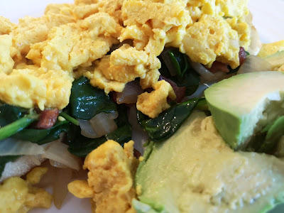 Scrambled eggs and spinach on an English muffin with avocado