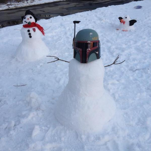 Three snowmen on a lawn: one with traditional buttons, hat, etc.; one made up to be a penguin; and one with Boba Fett helmet for head