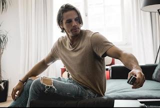 Foto de Yann Sommer,suíço, modelo, goleiro do time de futebol da Alemanha, canta, toca violão, e tem um blog de culinária. Yann está sentado em um estofado cinza, com o braço esquerdo no ar, segurando um celular abaixo, pronto para tirar uma selfie; o outro braço tatuado na parte interna estica-se em abertura e apoia a mão direita sobre a perna direita. Yann tem 29 anos, pele de cor clara, porte atlético, cabelos castanhos claros lisos e despenteados que modulam o rosto oval, sobrancelhas retas, olhos amendoados direcionados ao celular, nariz afilado e levemente arrebitado, lábios carnudos, bigode e barba por fazer. Yann usa uma camiseta de manga curta marrom claro, calça jeans desbotada com rasgos na altura dos joelhos. Ao fundo, uma cortina branca, à esquerda um vaso com planta alta e à direita, um abajur preto.