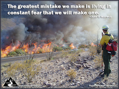 The greatest mistake we make is living in constant fear that we will make one. –John C. Maxwell (Wildland firefighter monitoring a fire along a road)