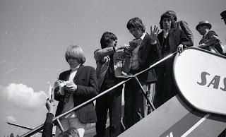 Fotografía en blanco y negro de los Rolling bajando las escaleras de una avión en Oslo