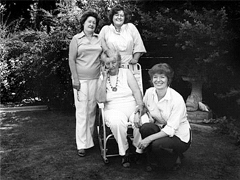 black and white snapshot of an elderly woman seated in a chair surrounded by three middle-aged women