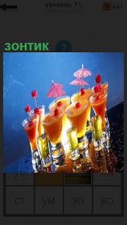 На столе стоят приготовленные коктейли с зонтиком сверху