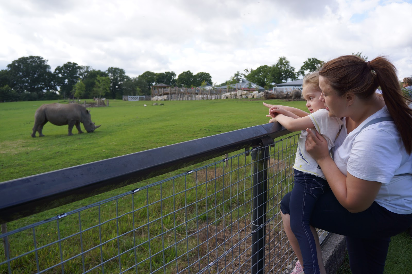 mum and daughter pointing at rhinos at marwell zoo