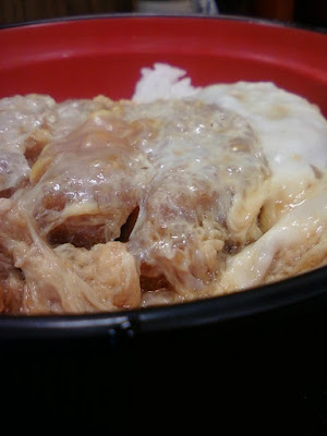 Katsudon is a pork cutlet served with egg and vegetables on top of a bowl of rice.