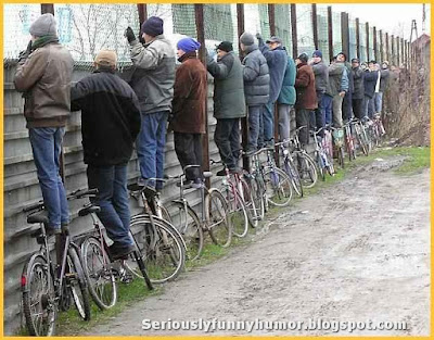 group-of-men-stands-on-bicycles-to-watch-over-fence-fun