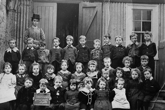 "Photograph of the Infants Class of Christ Church, Little Heath School, outside the ""iron room"" c1902"
