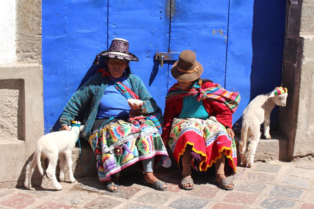 Locals against a blue door in Cusco, Peru - lifestyle & travel blog