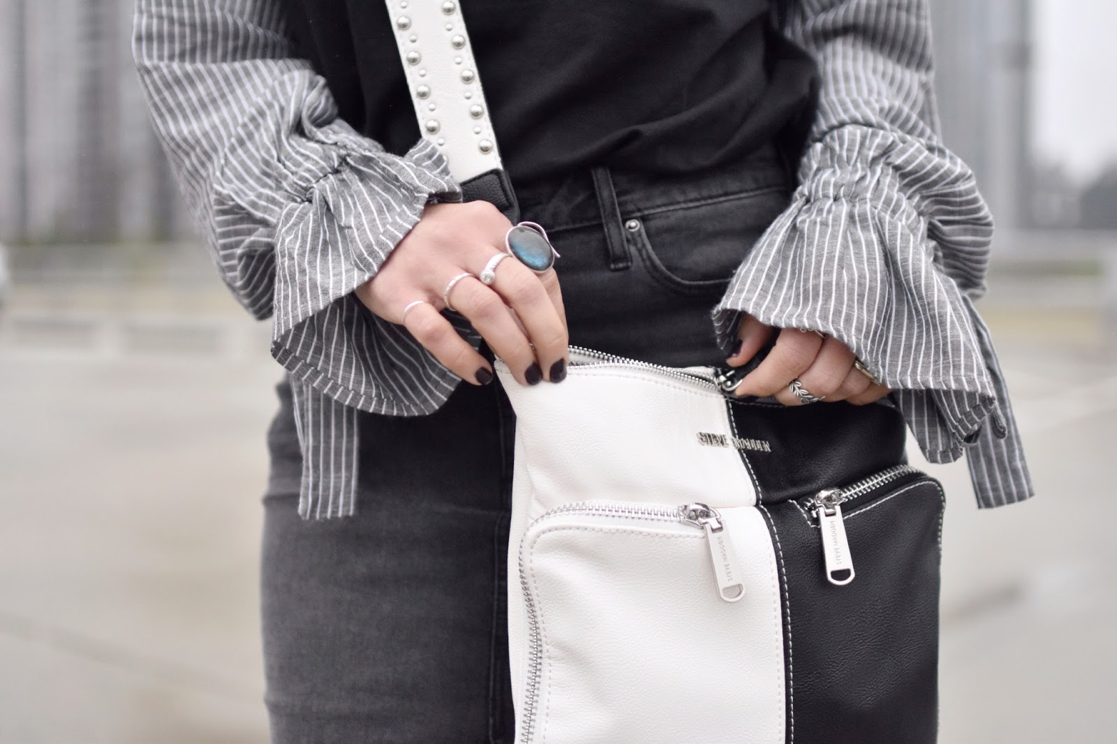Monika Faulkner outfit inspiration - sweatshirt with mixed media sleeves, black denim skirt, black and white cross-body bag