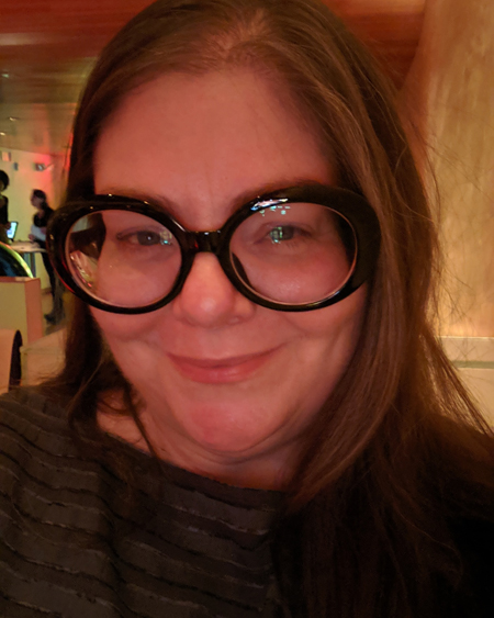 image of me from the shoulders up at a restaurant; I am smiling slightly with my hair down and wearing large black glasses and a slate grey top