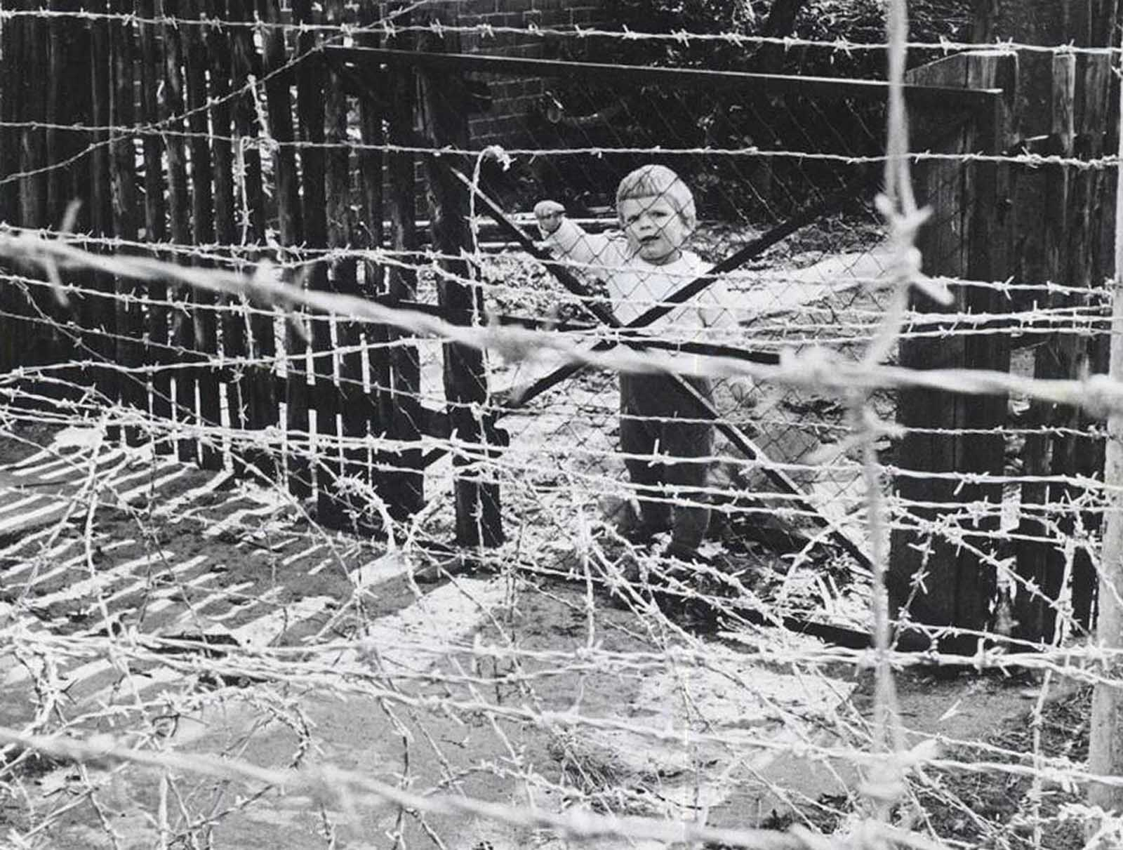 A young girl in the Eastern Sector looks through barbed wire into Steinstucken, Berlin, in October of 1961.