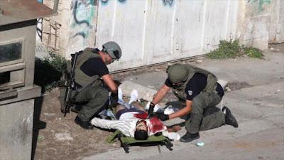 Fuerzas israelíes inspeccionan un palestino muerto a tiros en Cisjordania.