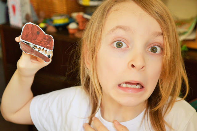 George holding a dino peg and pullnig a scared/shocked face.