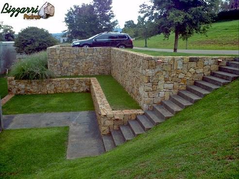 Entre a rua e a residência existia essa diferença de altura de mais de 4 m, construímos o muro de pedra com vários patamares integrando com a execução do paisagismo e o gramado com grama esmeralda.