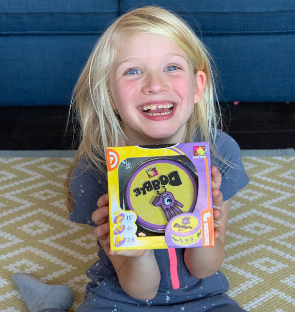 An excited child holding Dobble Family Card Game in it's packaging