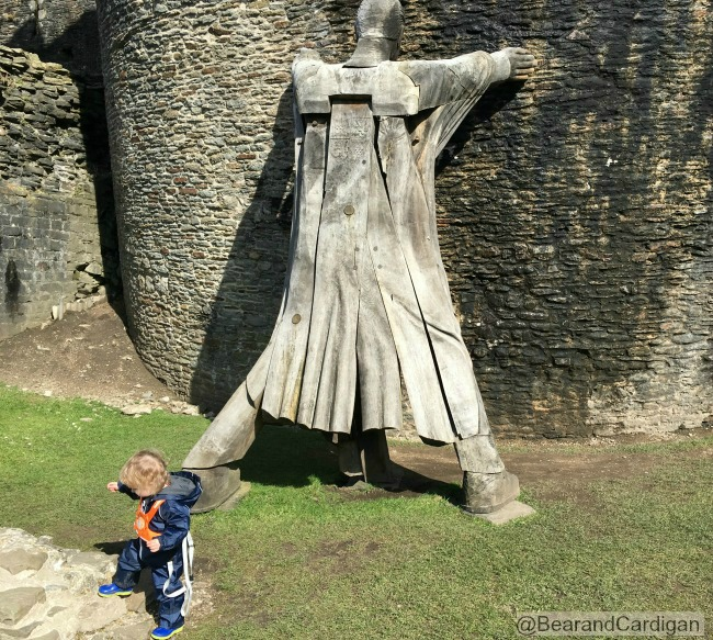 giant holding up castle. Toddler trying to climb stones