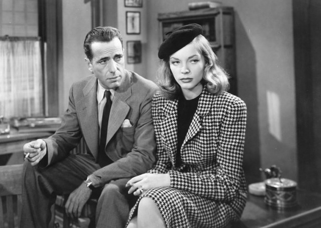 Humphrey Bogart and Lauren Bacall sitting on a desk