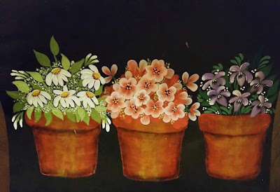Painted pots filled with painted Folk art flowers - daisies, geraniums and violets.