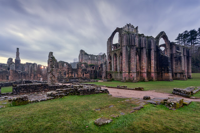 Magnificent ruins of Fountains Abbey under a stormy evening sky in North Yorkshire