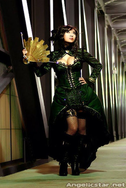 Asian steampunk woman cosplaying as a madam in an opium den in china. green steampunk dress, hat, jacket, metal steampunk fan, boots, fishnets