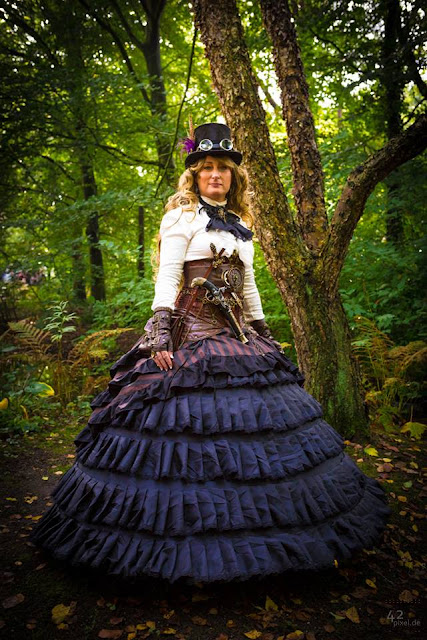 Steampunk woman wearing a victorian era purple skirt with a corset, top hat, goggles and jabot. Women's steampunk fashion and costumes.