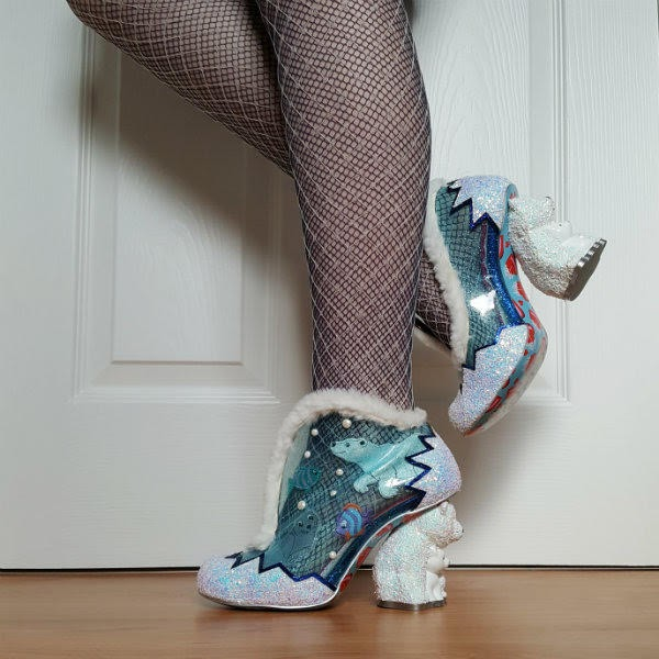 leg lifted wearing white glitter polar bear heeled shoes with blue sheer uppers and sea animal applique