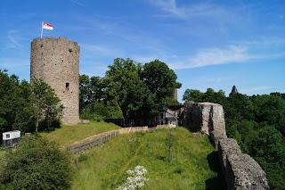 Eine Burgruine. Auf dem Bergfried weht eine Fahne. Die gesamte Ruine ist mit Grad bewachsen.