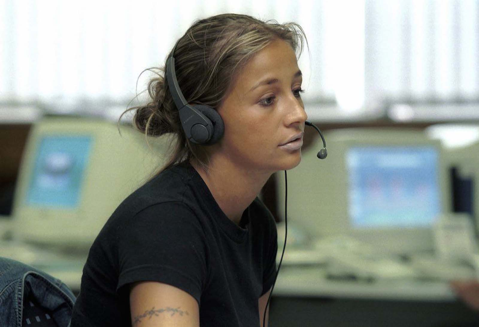 Woman in a call center in Germany. Her highlighted hair is worn back in a low messy bun. She wears very light-coloured lipstick, a black T-shirt with a denim jacket on the back of her chair. A tattoo encircles her right upper arm. 1999.