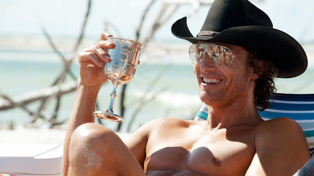 Matthew McConaughey shirtless in a cowboy hat drinking out of a chalice.