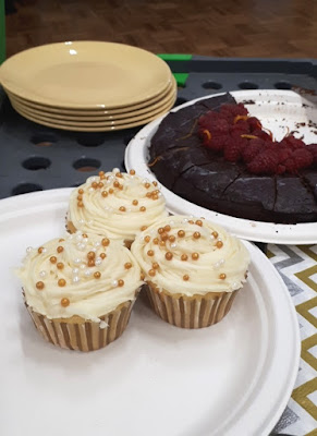 Plate of cupcakes next to a plate holding half a dark chocolate cake with fresh raspberries on the top of it. Next to the cake is a stack of plates, and in front is a stack of paper napkins.