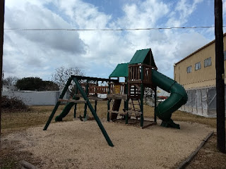 large playground climbing structure with slides and swings