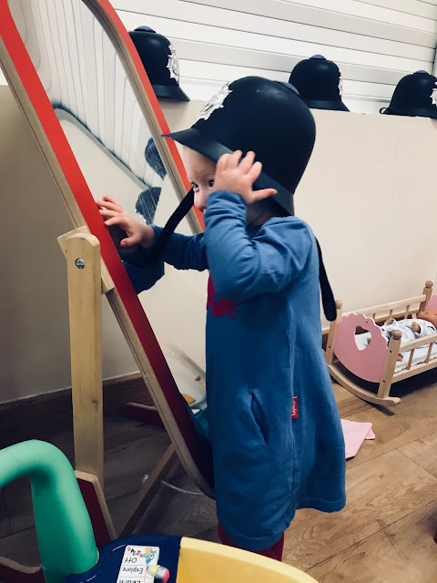 A toddler trying on a toy policeman's hat in front of a full length children's mirror