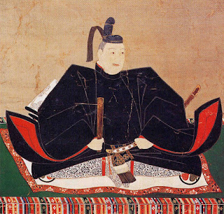 Portrait of the 17th century Japanese Shogun, Tokugawa Hidetada. He is wearing a black coat with a red lining and a small black hat.
